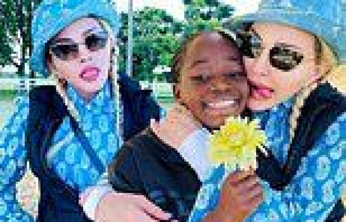 Madonna sticks out her tongue and cuddles up to her beaming daughter Estere