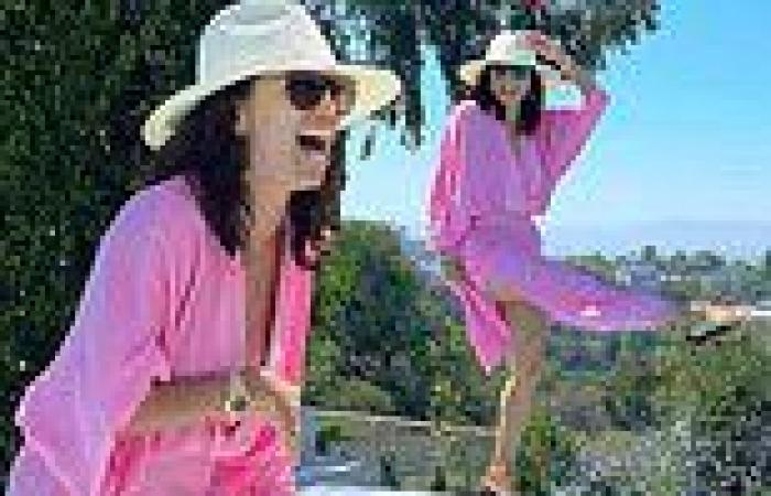 Eva Longoria is in high spirits as she poses next to a pool in a summery pink ...