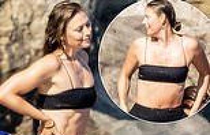 Maria Sharapova shows off her enviably toned abs in a black bikini