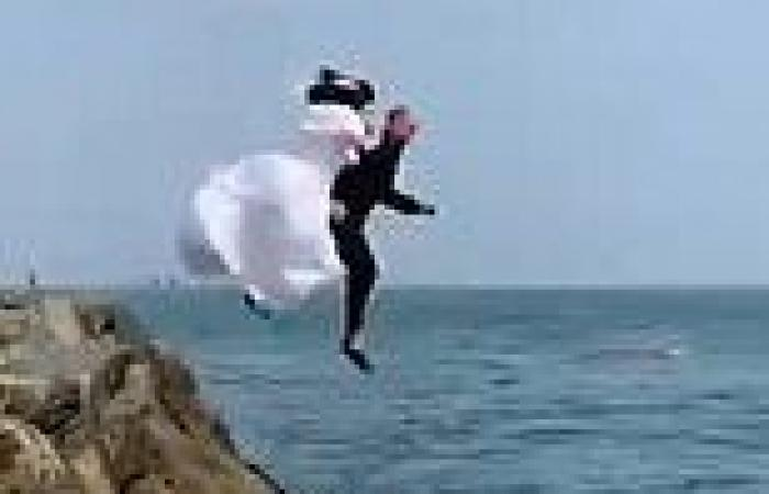 Bride and groom celebrate marriage by jumping into the Irish Sea wearing their ...