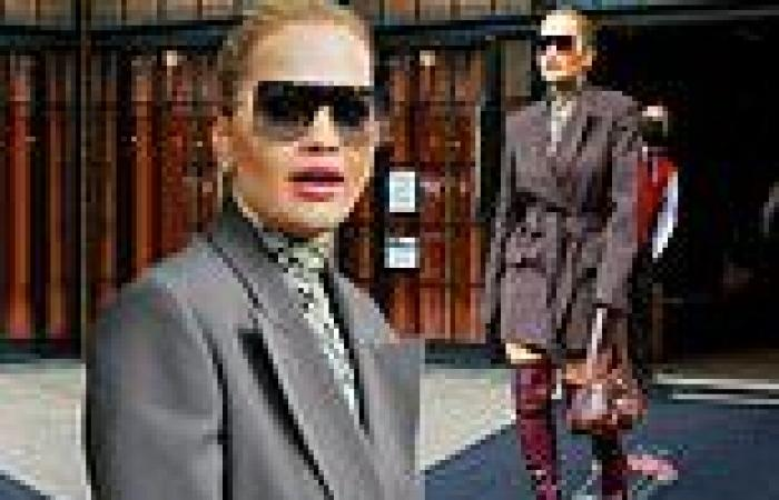 Rita Ora wows in a grey trench coat, knee-high boots and edgy sunglasses