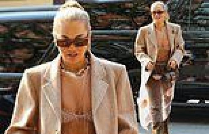 Rita Ora showcases her toned abs in a sheer veil and beige bra as she steps out ...