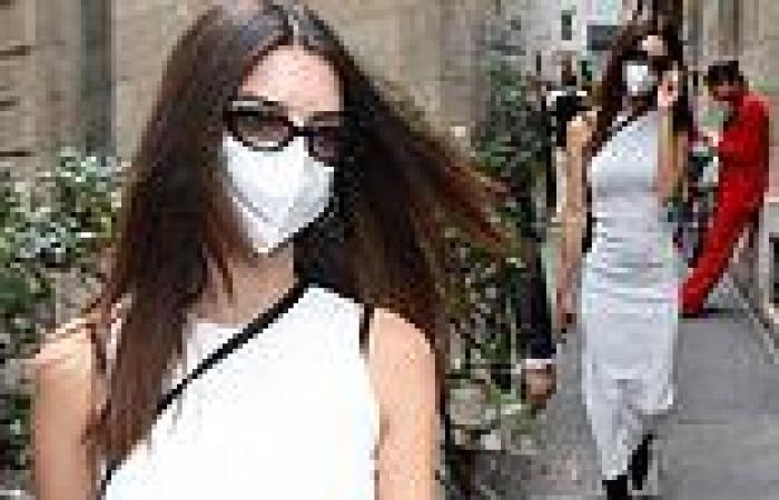 Emily Ratajkowski showcases her svelte waist in a white maxi dress during a ...
