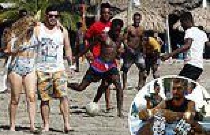 Tourists breeze past Hattian migrants playing soccer on a Colombia beach