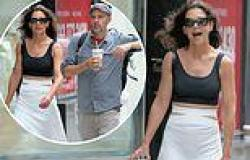 Katie Holmes stuns in a black tank top and flowing white pants while stepping ...